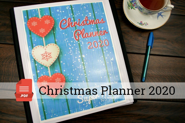 Christmas Planner 2020 Binder on a table with a blue pen and a cup of tea.