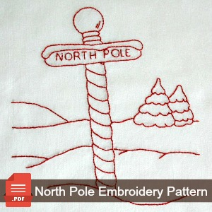 Embroidered pattern of the North Pole with snow and pine trees